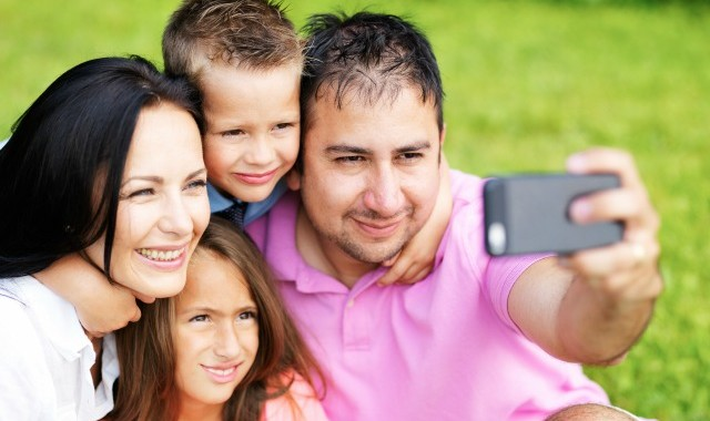 family taking selfies with smartphone in park