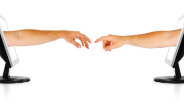 Two human hands coming out two seperate computer monitors, reaching out for each other. Isolated on a white background